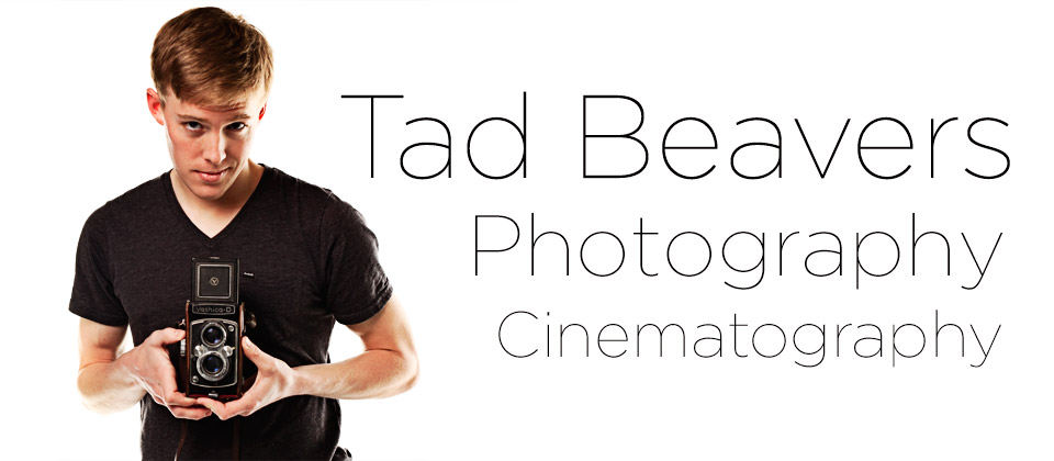 Tad Beavers holding an older camera on white